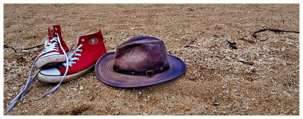 Trampki i kapelusz leżą na piasku. Na plaży pełno jest kamieni i muszel. Trampki są rozwiązane.